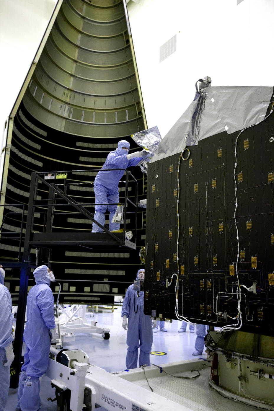 Inside the Payload Hazardous Servicing Facility at NASA's Kennedy Space Center in Florida, engineers and technicians prepare the Mars Atmosphere and Volatile Evolution, or MAVEN, spacecraft for encapsulation inside its payload fairing.