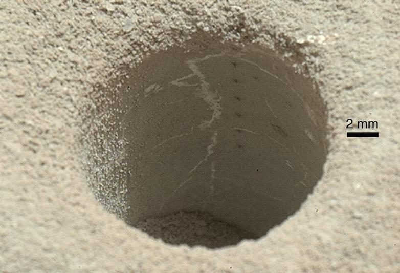 "The hole that NASA's Curiosity Mars rover drilled into target rock ""John Klein"" provided a view into the interior of the rock, as well as obtaining a sample of powdered material from the rock."