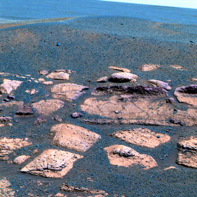 "This false color image suggests that the plains beyond the small crater where the Mars Exploration Rover Opportunity now sits are littered with the same dark grey material found inside the crater in the form of spherules or ""blueberries."""