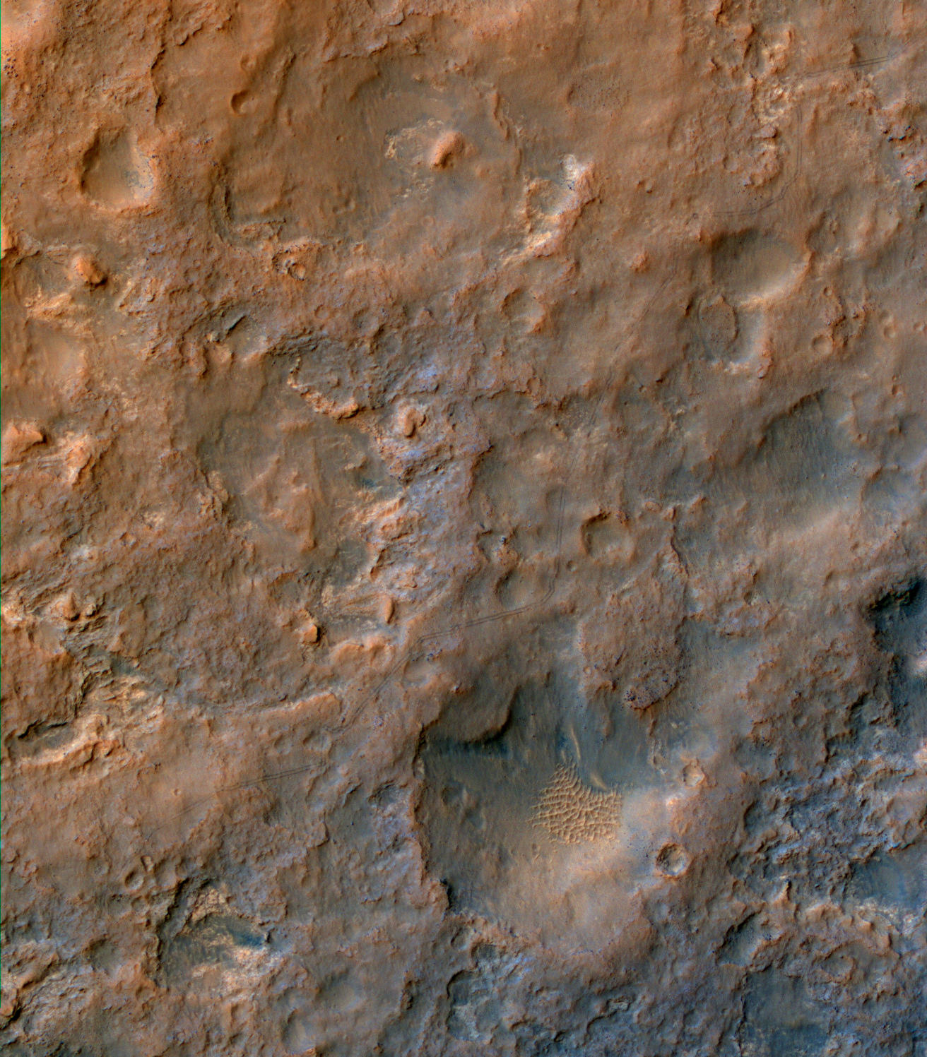Two parallel tracks left by the wheels of NASA's Curiosity Mars rover cross rugged ground in this portion of a Dec. 11, 2013, observation by the High Resolution Imaging Science Experiment (HiRISE) camera on NASA's Mars Reconnaissance Orbiter.