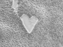 The Mars Global Surveyor (MGS) Mars Orbiter Camera (MOC) captured this unique view of a bright, heart-shaped mesa in the south polar region on November 26, 1999.  The presence of this mesa indicates that the darker, rough terrain that surrounds it was once covered by a layer of the bright material.
