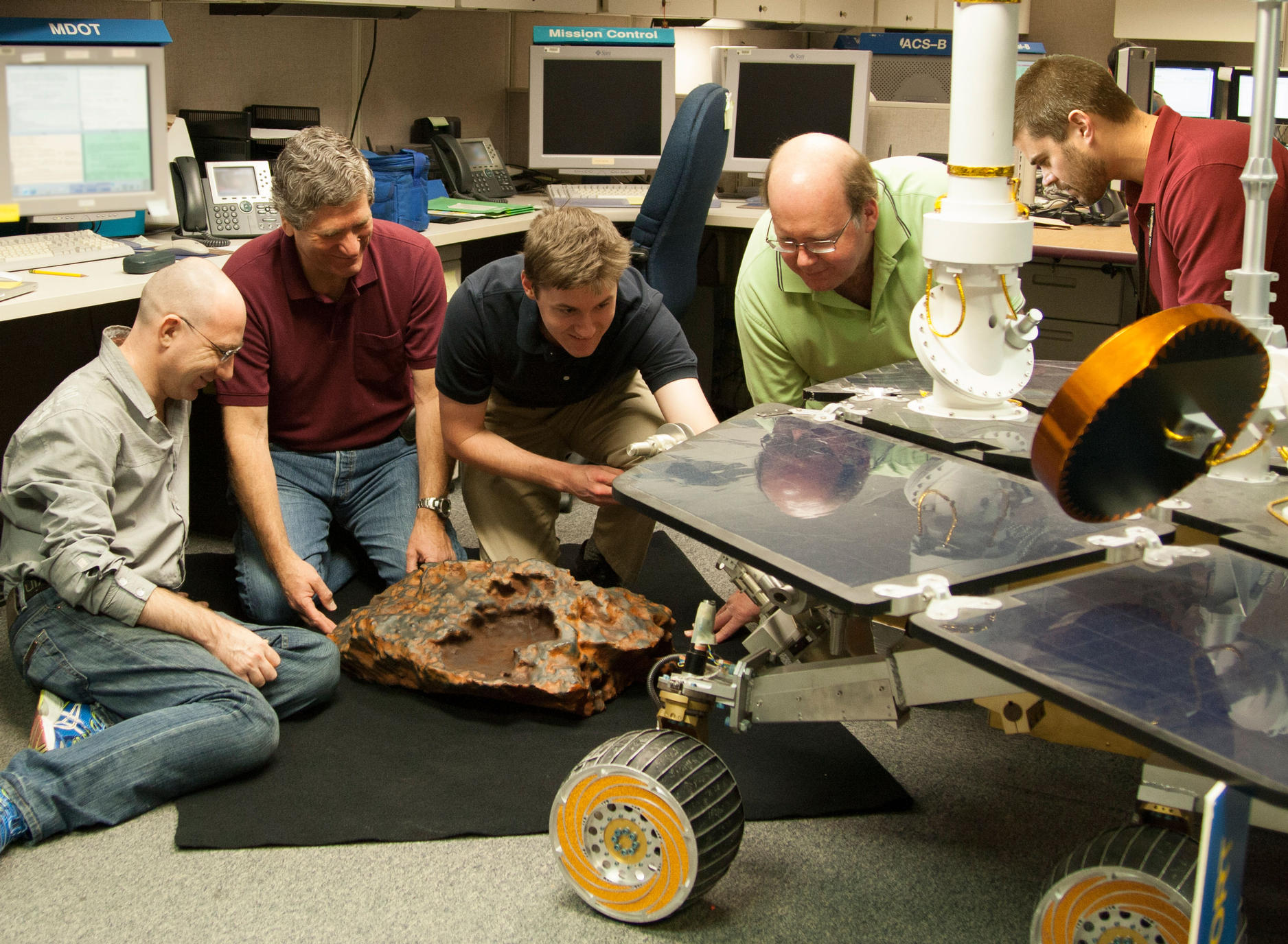Researchers with Meteorite and Rover Models