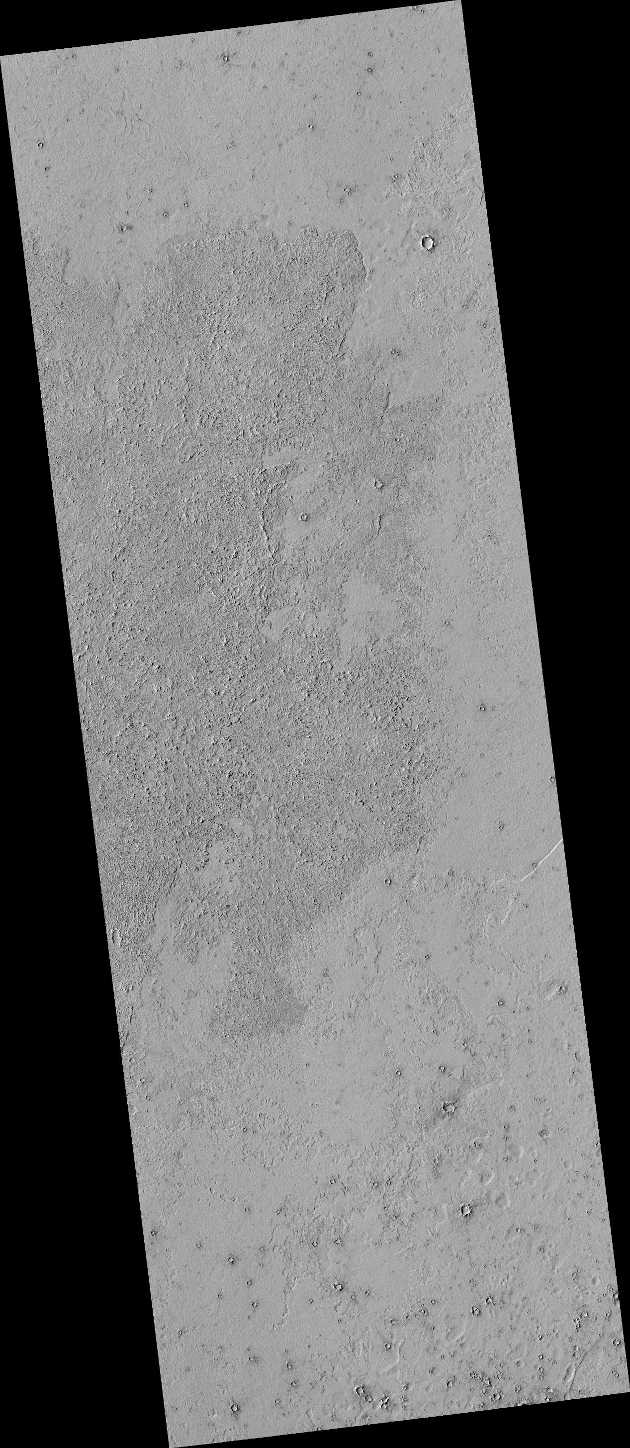 This image shows details of the lava covered plains near the equator of Mars. The darker looking area has a rough lava surface with all the shadows giving the region a darker appearance.