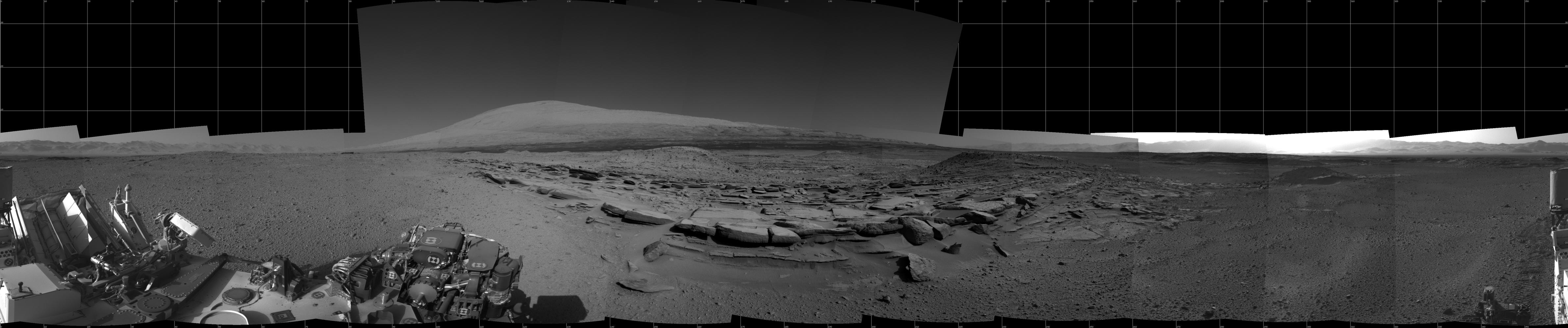"This view from NASA's Curiosity Mars rover spans 360 degrees, centered southward toward a planned science waypoint at ""the Kimberley,"" with an outcrop of eroded sandstone in the foreground. It combines several frames taken by the Navigation Camera on March 18, 2014."