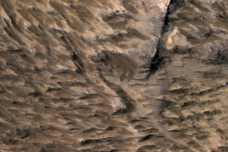 This April 6, 2014, image from the High Resolution Imaging Science Experiment (HiRISE) camera on NASA's Mars Reconnaissance Orbiter shows numerous landslides in the vicinity of where an impact crater was excavated in March 2012.