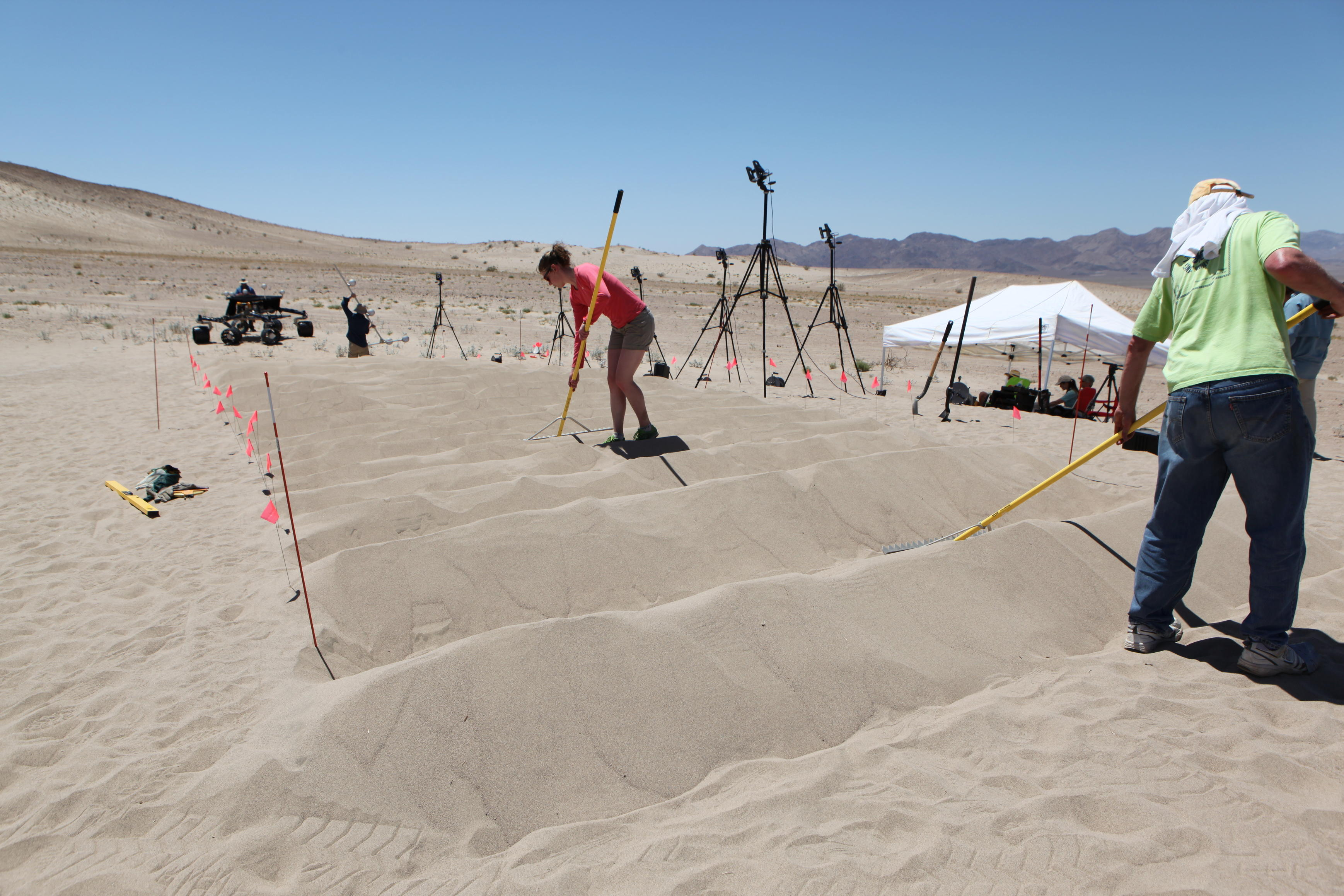 sand dune, mars rover, wheel, Dumont, Scarecrow, test - This image shows a row of uphill, white sand dunes that JPL engineers shape with long rakes for desert rover test, under blue skies.  The Scarecrow rover sits at the bottom, waiting to be tested.