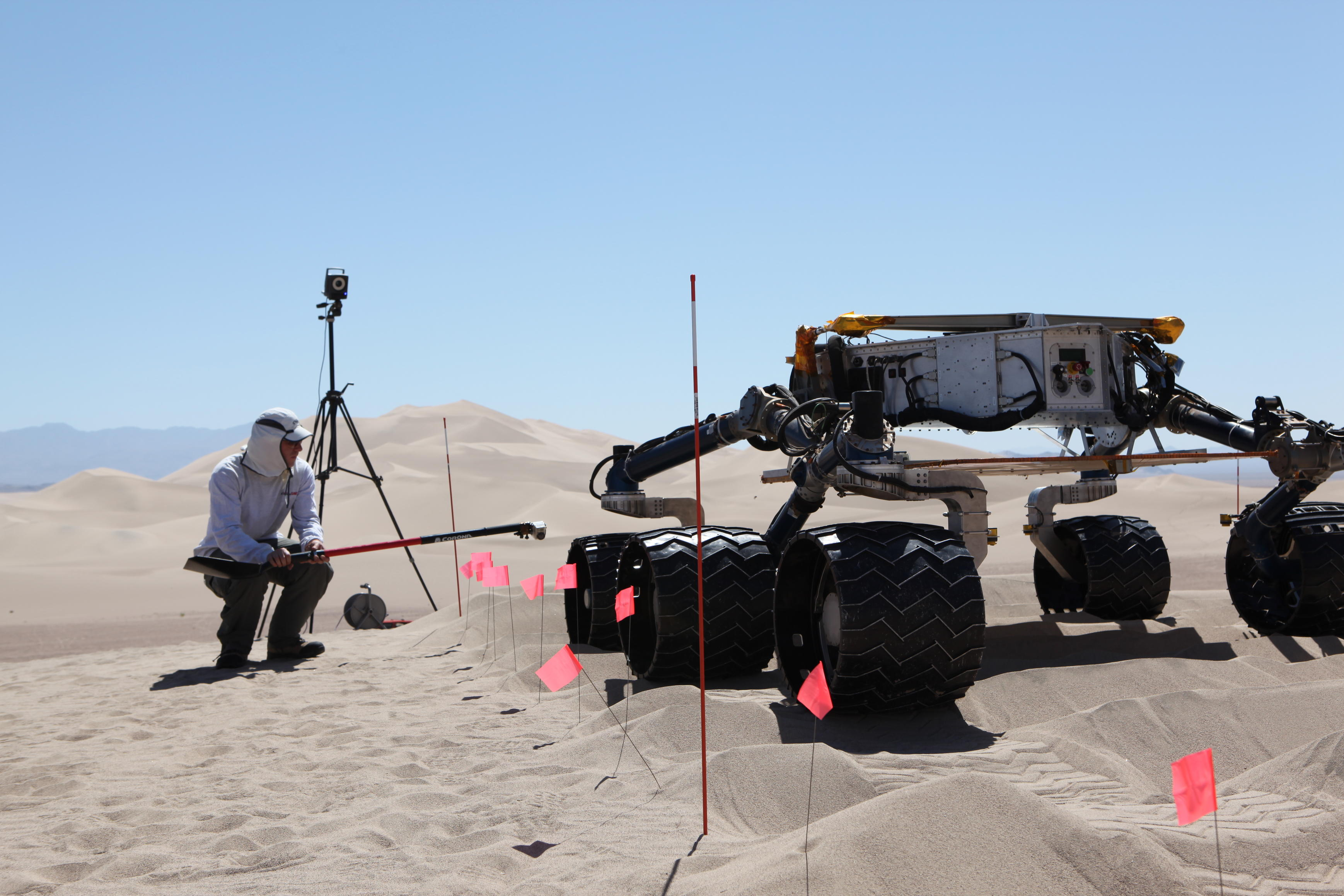 sand dune, mars rover, wheel, Dumont, Scarecrow, test - This image shows the scarecrow test rover going over a dunes obstacle course, while an engineer hunches down to see the wheels as it drives.