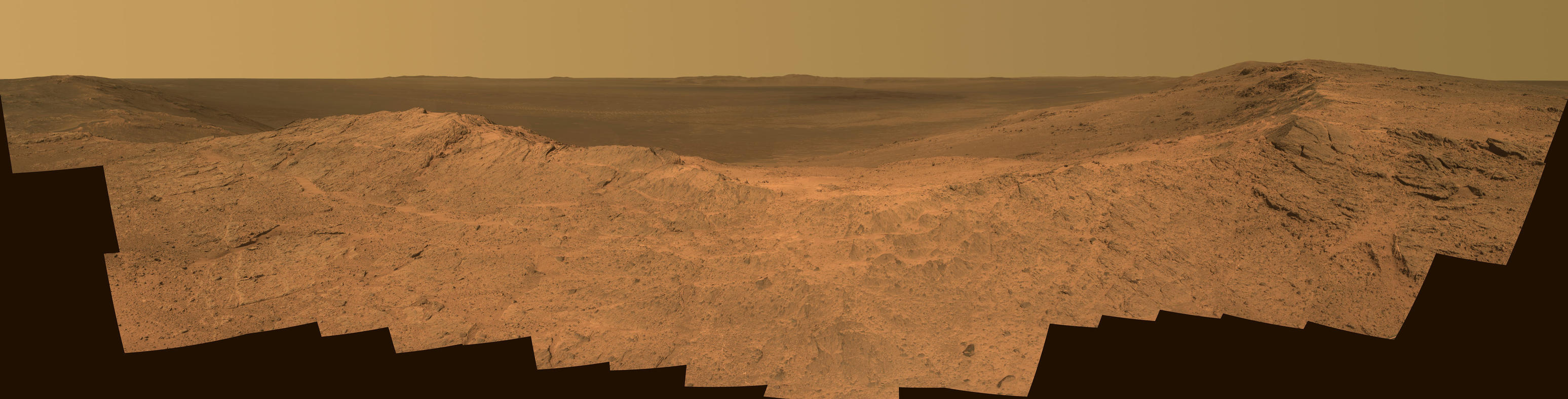"This scene from the panoramic camera (Pancam) on NASA's Mars Exploration Rover Opportunity catches ""Pillinger Point,"" on the western rim of Endeavour Crater, in the foreground. The eastern rim of the crater is on the distant horizon. The scene merges many Pancam exposures taken on May 14, 2014."