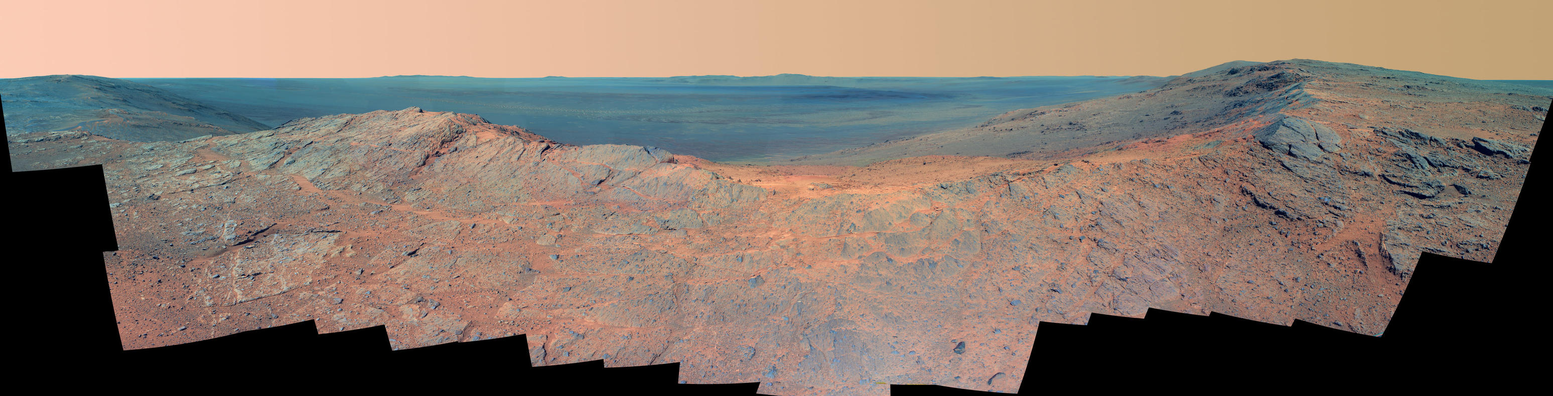 "This May 14, 2014, scene from the Pancam on NASA's Mars Exploration Rover Opportunity catches ""Pillinger Point,"" on the western rim of Endeavour Crater, in the foreground and the crater's eastern rim on the horizon. The scene's false color makes differences in surface materials more easily visible."