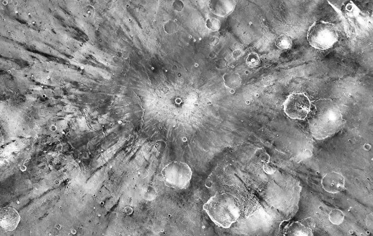 A small impact crater on Mars named Gratteri, 4.3 miles (6.9 km) wide, lies at the center of large dark streaks.