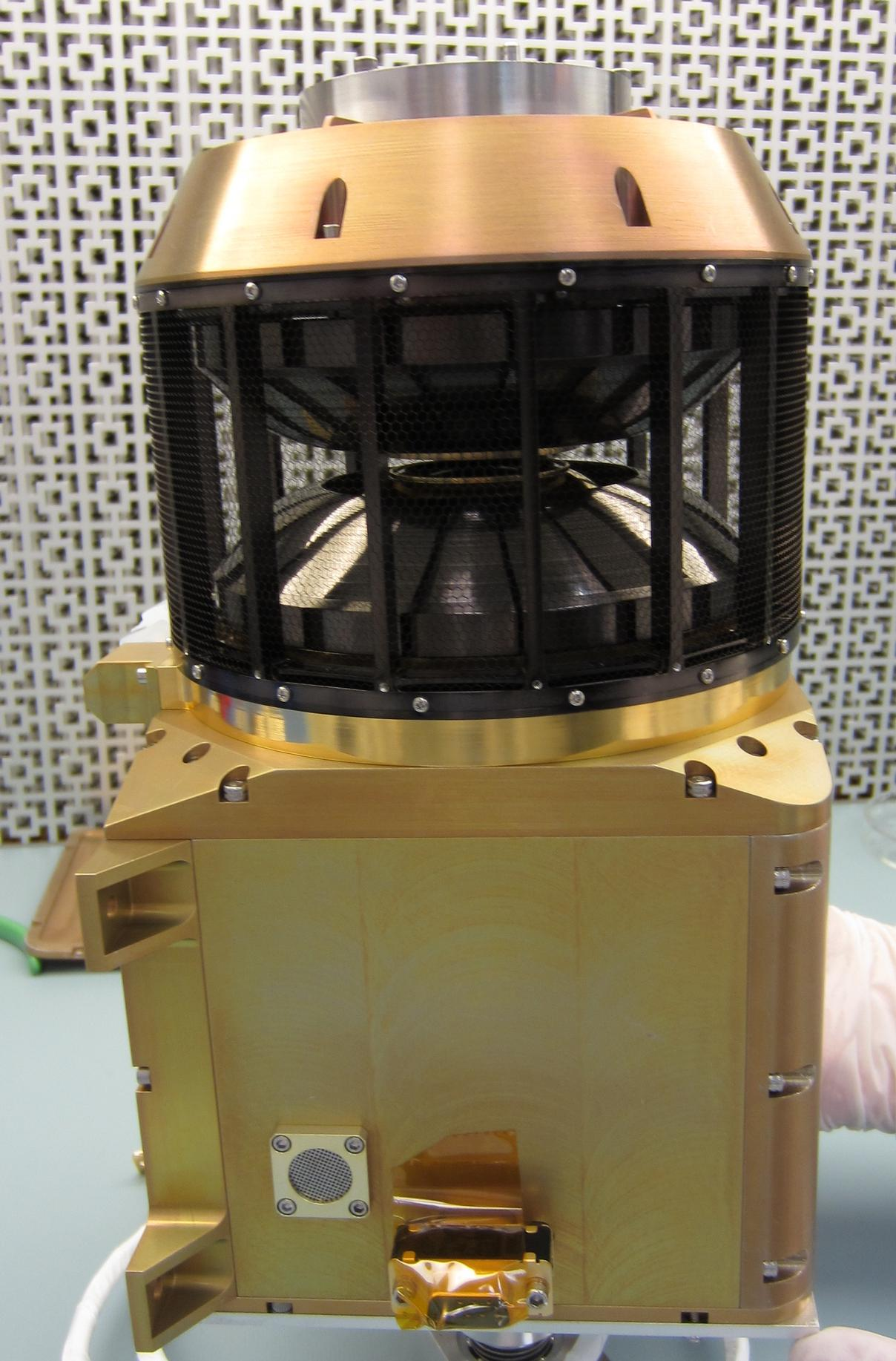 This image shows the wind analyzer instrument box that is yellow metal at the bottom, the top is a circular black cylinder.  The whole instrument is the size of a shoebox.