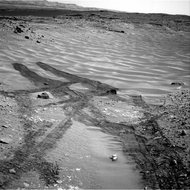 "This image from NASA's Curiosity Mars rover looks down the ramp at the northeastern end of ""Hidden Valley"" and across the sandy-floored valley to lower slopes of Mount Sharp on the horizon."