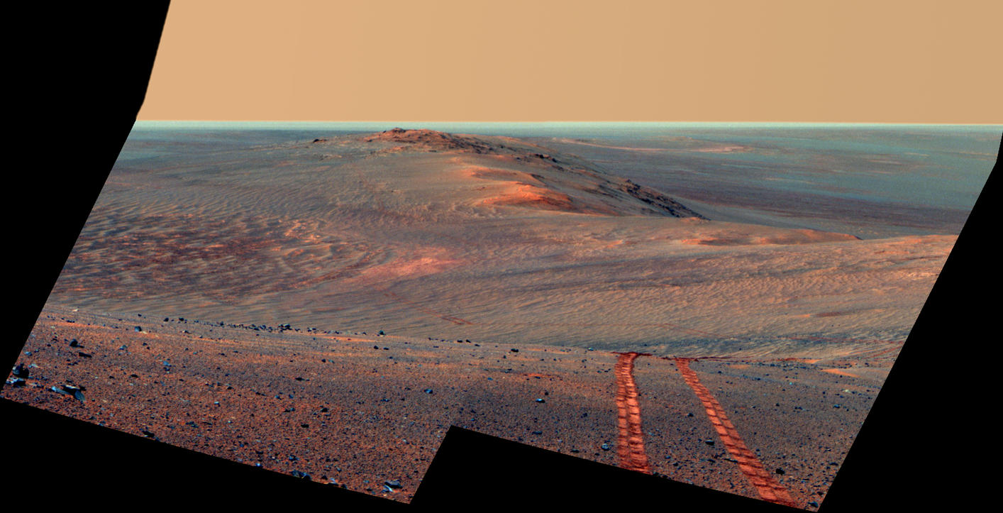 This Aug. 15, 2014, scene from the Pancam on NASA's Mars Exploration Rover Opportunity looks back toward part of the west rim of Endeavour Crater that the rover drove along, heading southward, during the summer of 2014. This version is in false color, making the rover's wheel tracks more apparent.