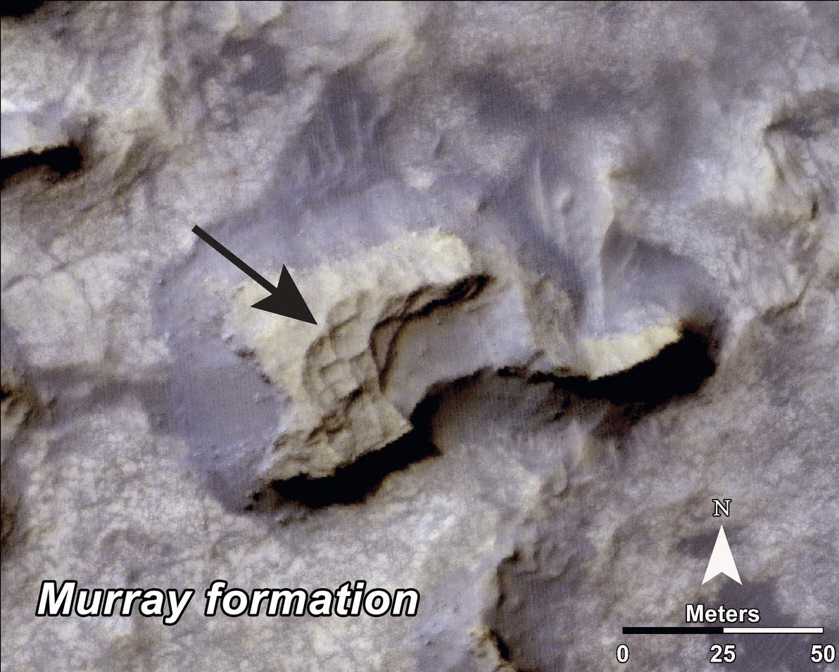 "This image shows a mesa (grayish) within the ""Murray Buttes"" area on Mars showing a complex fracture pattern (black arrow) protruding from the eroding rock."