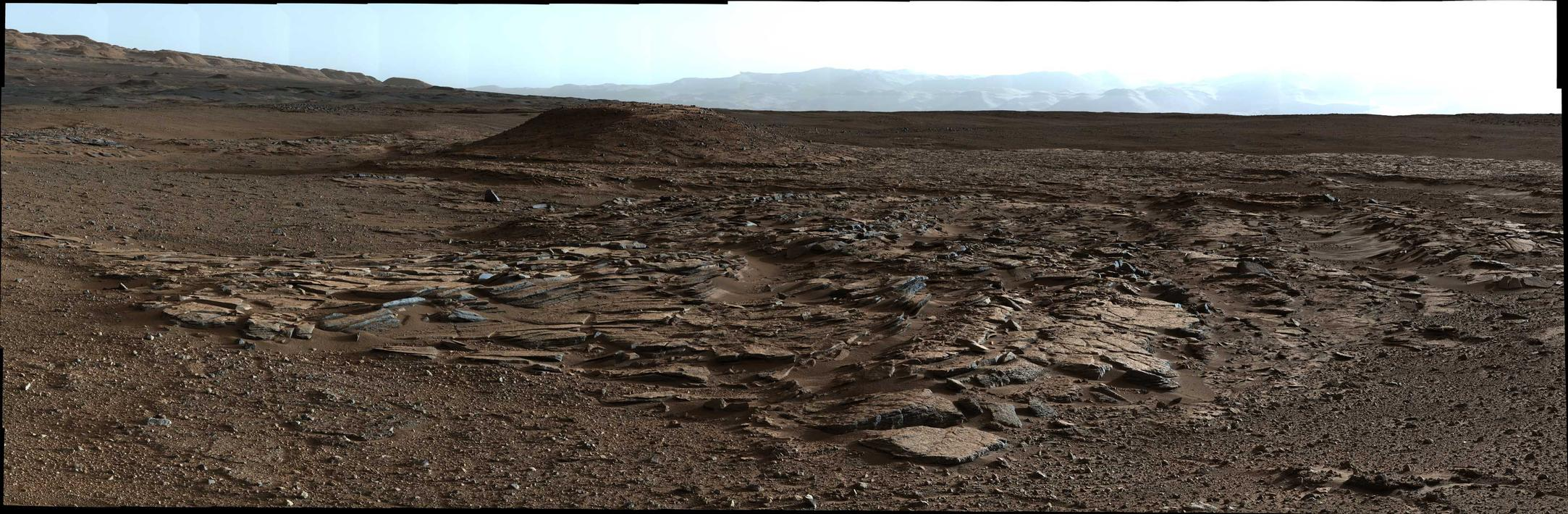 This April 4, 2014, image from Curiosity's Mastcam looks to the west of a waypoint on the rover's route to Mount Sharp. The mountain lies to the left of the scene. The image shows sets of sandstone beds inclined to the south (left), indicating progressive build-out of sediment toward Mount Sharp.