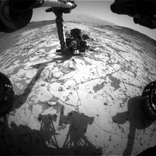 "This view from the wide-angle Hazard Avoidance Camera on the front of NASA's Curiosity Mars Rover shows the rover's drill in position for a mini-drill test to assess whether a rock target called ""Mojave"" is appropriate for full-depth drilling to collect a sample.  It was taken on Jan. 13, 2015."