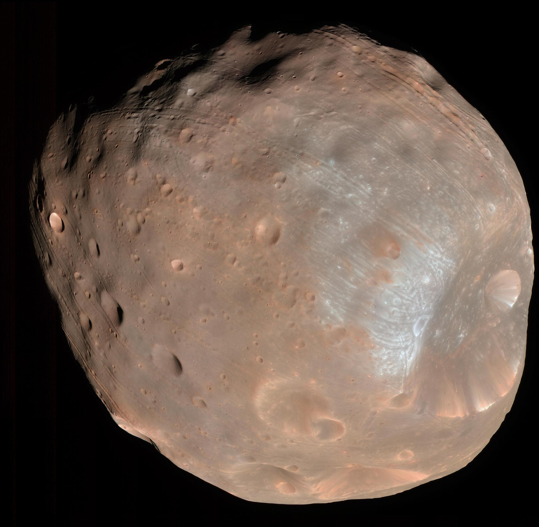 This is a color image of the largest of Mars' two moons, Phobos.  It appears pinkish in color with a giant crater dent on the far, right-side.  The crater edges seem whiter than the rest of the image.
