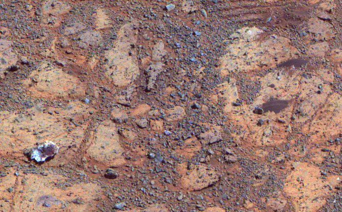 "A rock with a white edge and a red center reminds us of a jelly donut in a box from the local donut shop in this image taken by Opportunity on February 4, 2014.  Named ""pinnacle Island"" by Opportunity's science team, this rock mysteriously appeared in an image where it had not been 4 days earlier.  Scientists believe that opportunity drove over and broke a rocks in the upper part of this image, sending that piece of pastry rolling downhill."