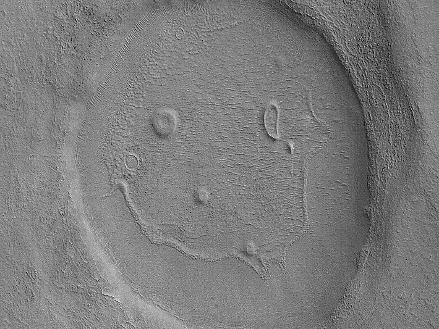"This picture of a crater resembling a ""happy face"" was taken by the Mars Reconnaissance Orbiter's Context Camera. The unnamed crater is almost 2 miles (about 3 kilometers) across  That's a BIG smile!"