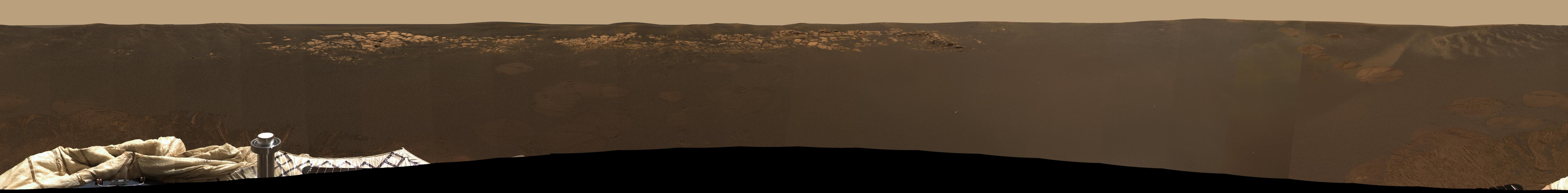 This expansive view of the martian real estate surrounding the Mars Exploration Rover Opportunity is the first 360 degree, high-resolution color image taken by the rover's panoramic camera.