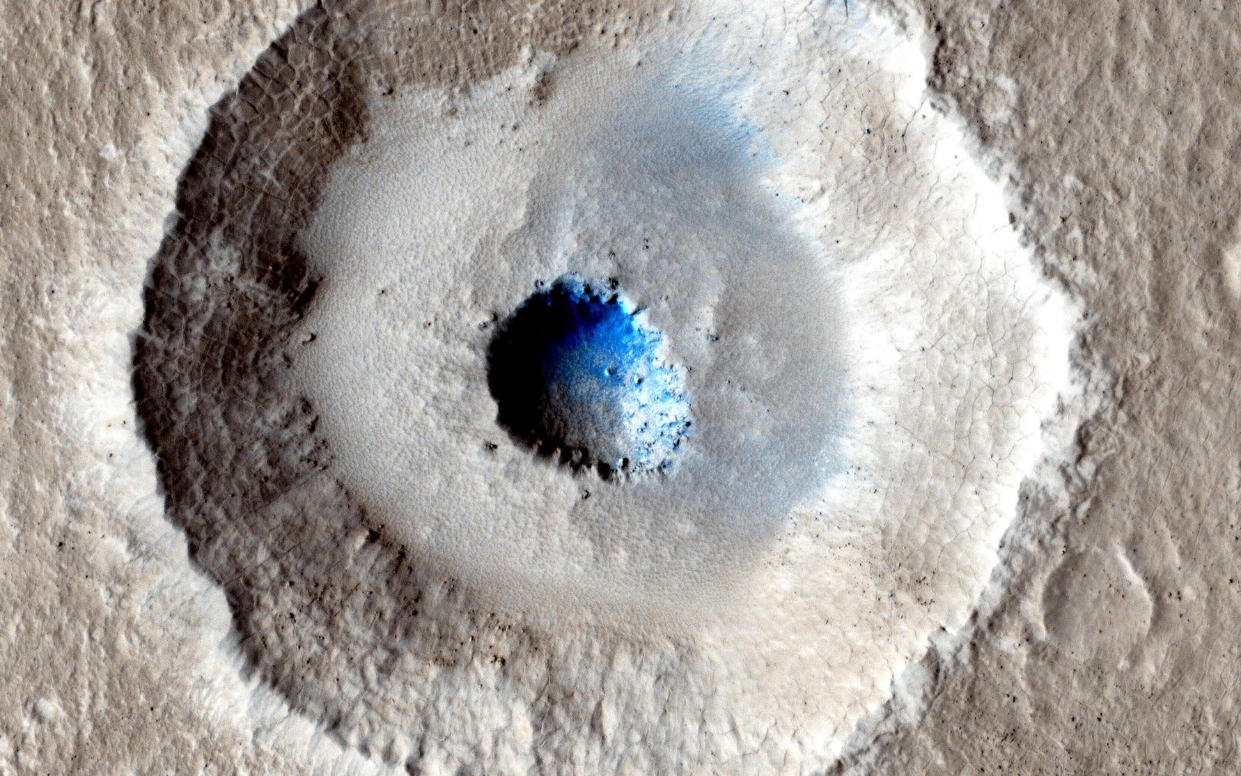 This is an image of a small, gray impact crater with a bowl-shaped rim.