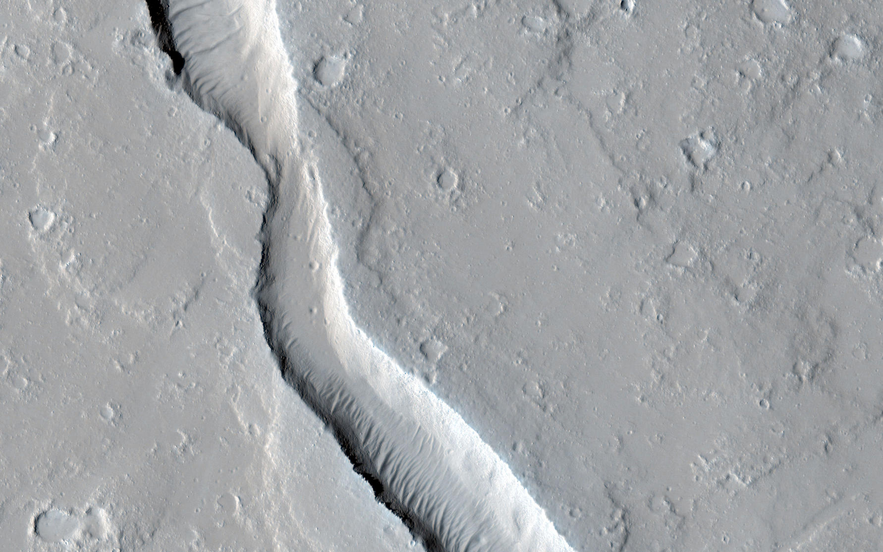 This image shows a lava channel, which lies just to the east of the largest volcano in the solar system: Olympus Mons.