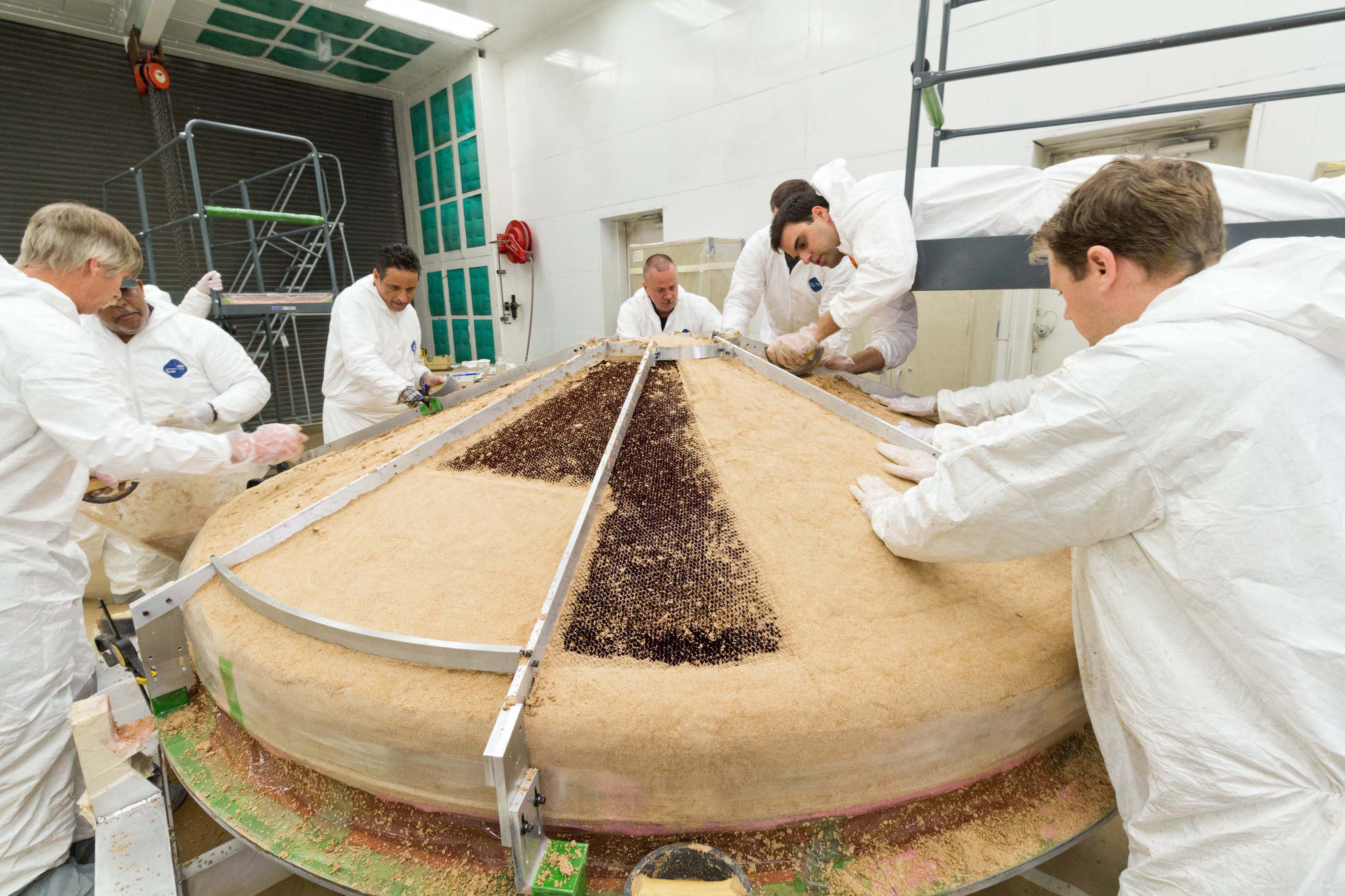 In this February 2015 scene from a clean room at Lockheed Martin Space Systems, Denver, specialists are building the heat shield to protect NASA's InSight spacecraft when it is speeding through the Martian atmosphere.