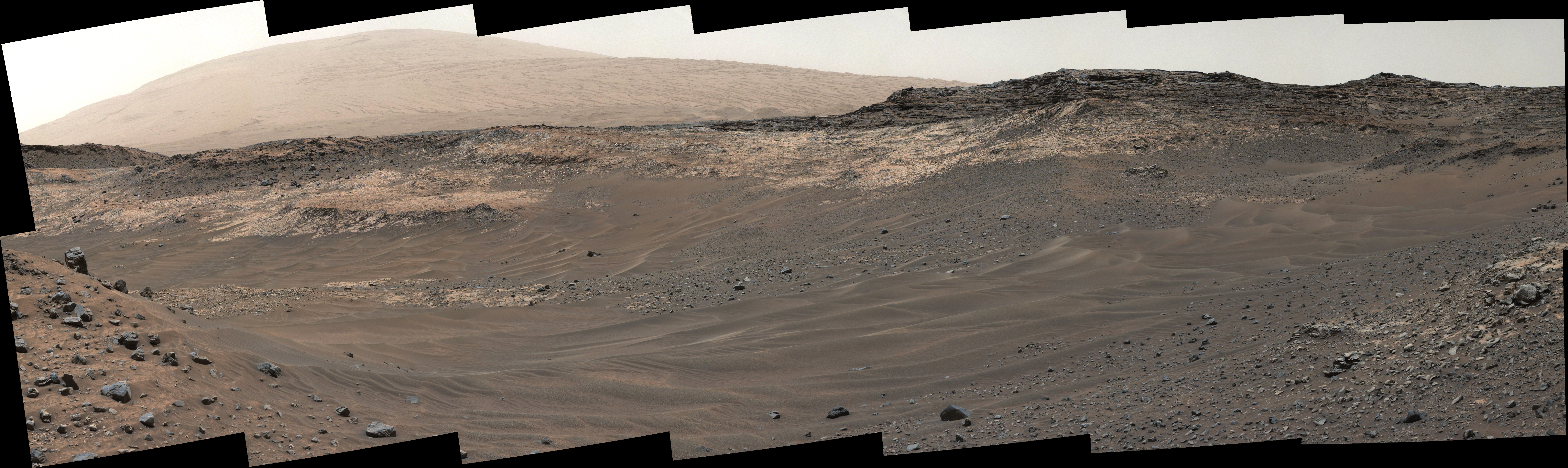 This May 10, 2015, view from Curiosity's Mastcam shows terrain judged difficult for traversing between the rover and an outcrop in the middle distance where a pale rock unit meets a darker rock unit above it. The rover team decided not to approach this outcrop and identified an alternative.