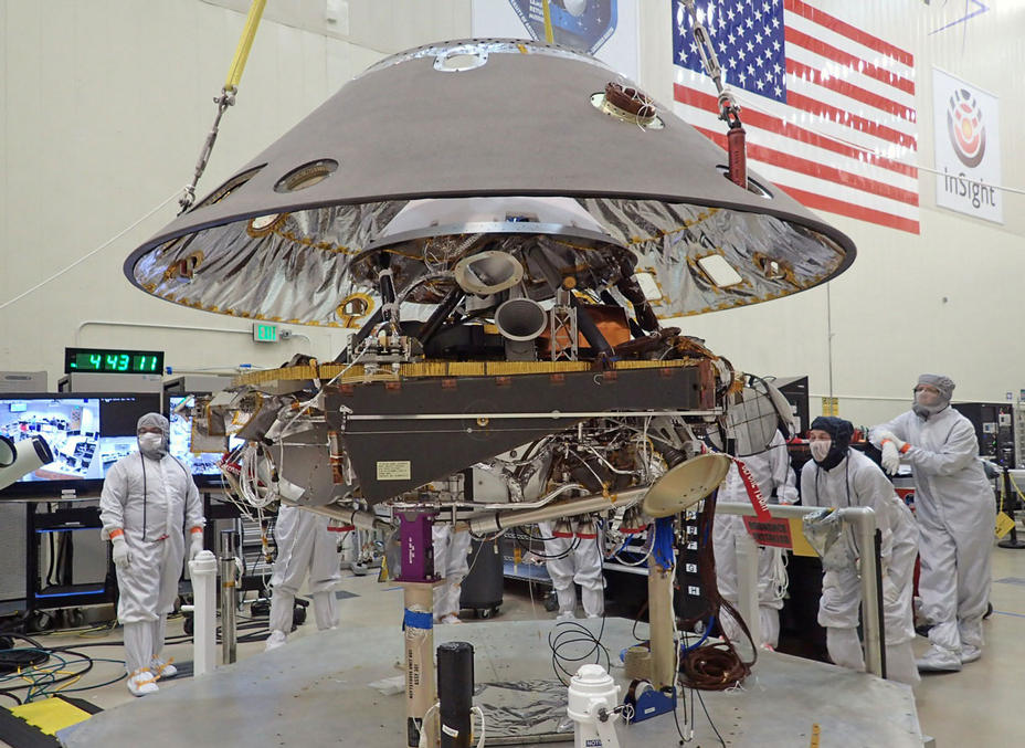 In this photo, the back shell of NASA's InSight spacecraft is being lowered onto the mission's lander, which is folded into its stowed configuration.