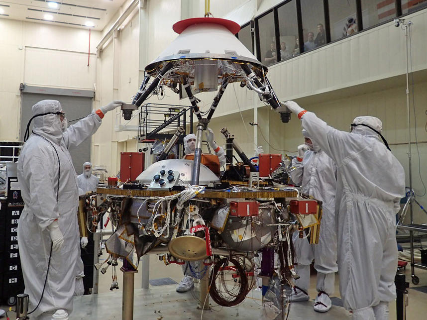 In this photo, spacecraft specialists at Lockheed Martin Space Systems, Denver, are reaching up to guide lowering of the parachute cone for installation onto NASA's InSight spacecraft.