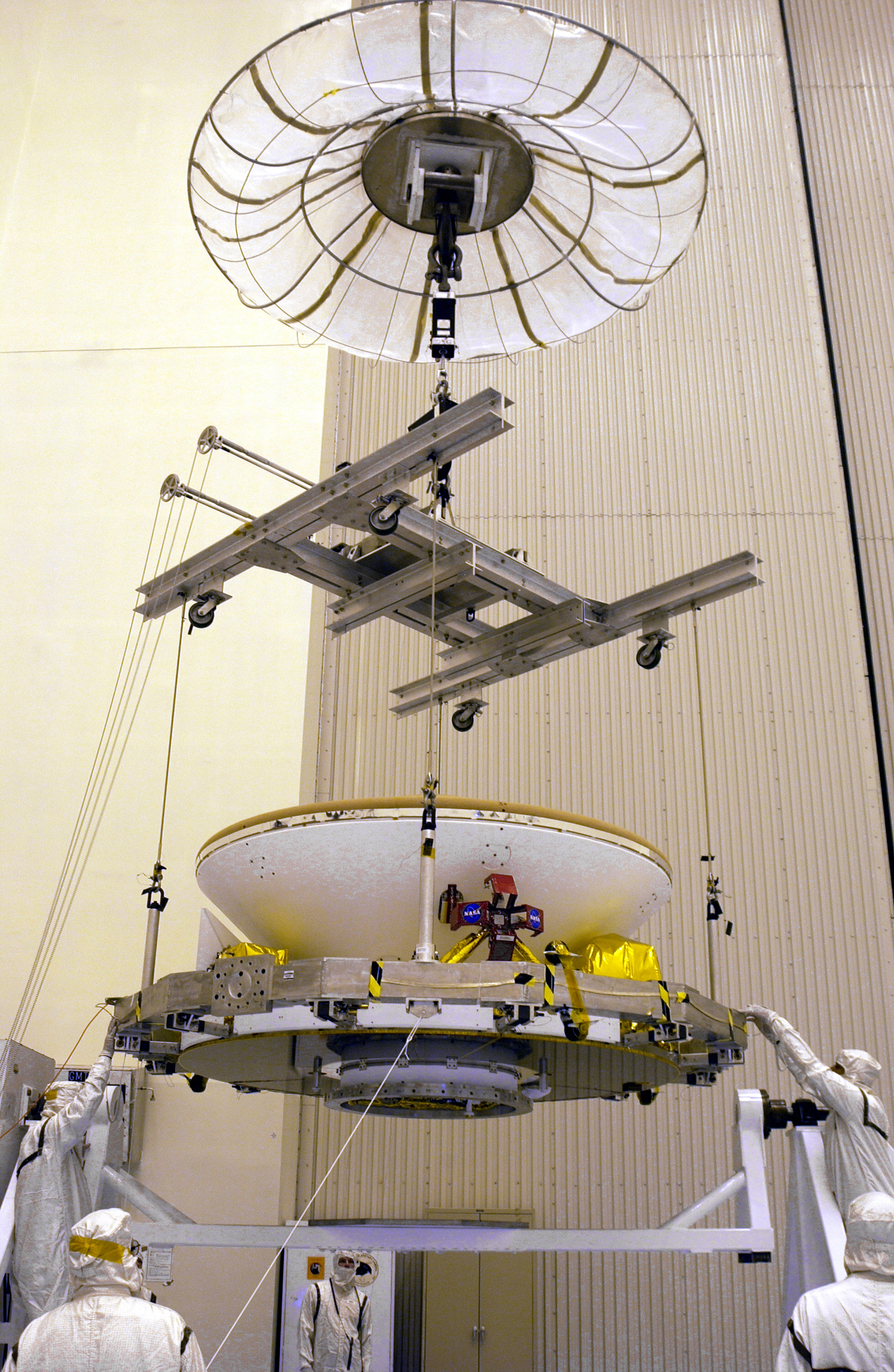In the Payload Hazardous Servicing Facility, an overhead crane lowers the Mars Exploration Rover (MER) aeroshell toward a rotation stand.