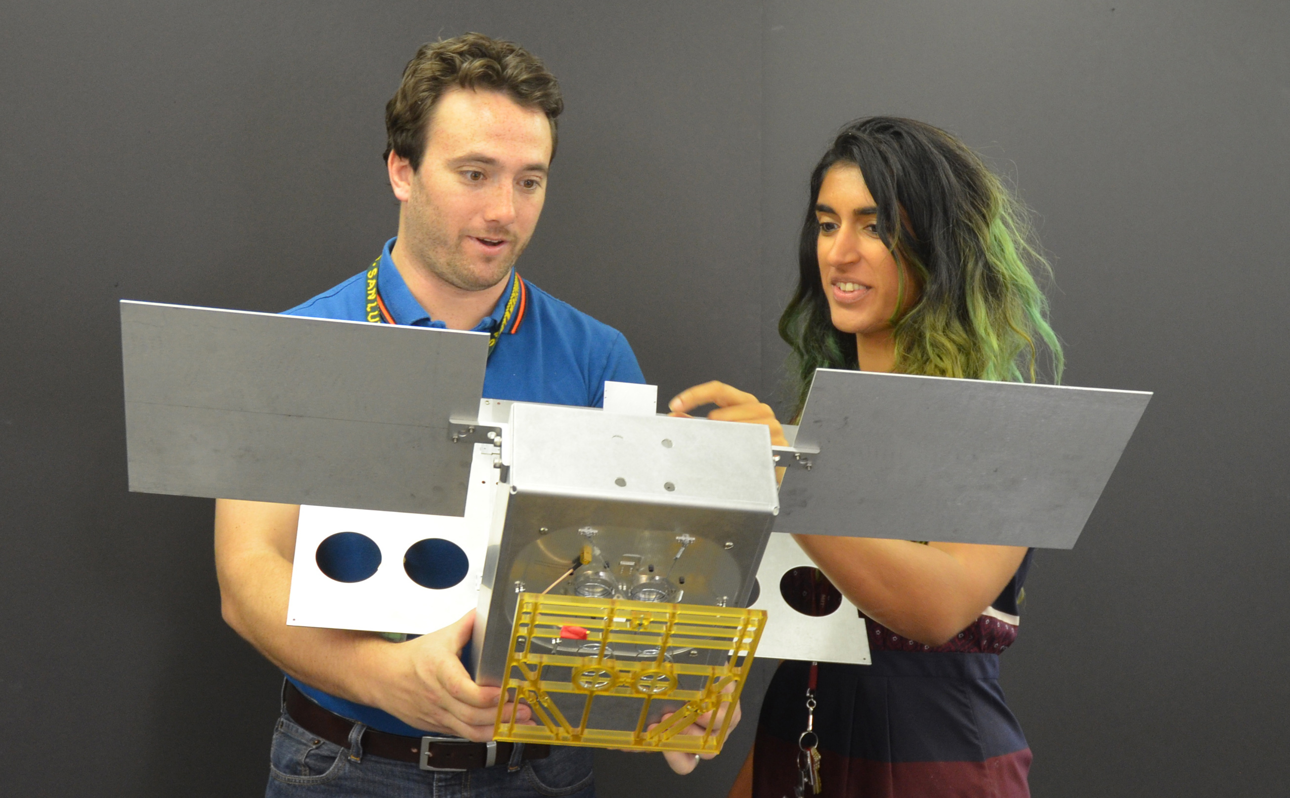 Two engineers hold a full-scale mechanical mock-up of a small satellite.