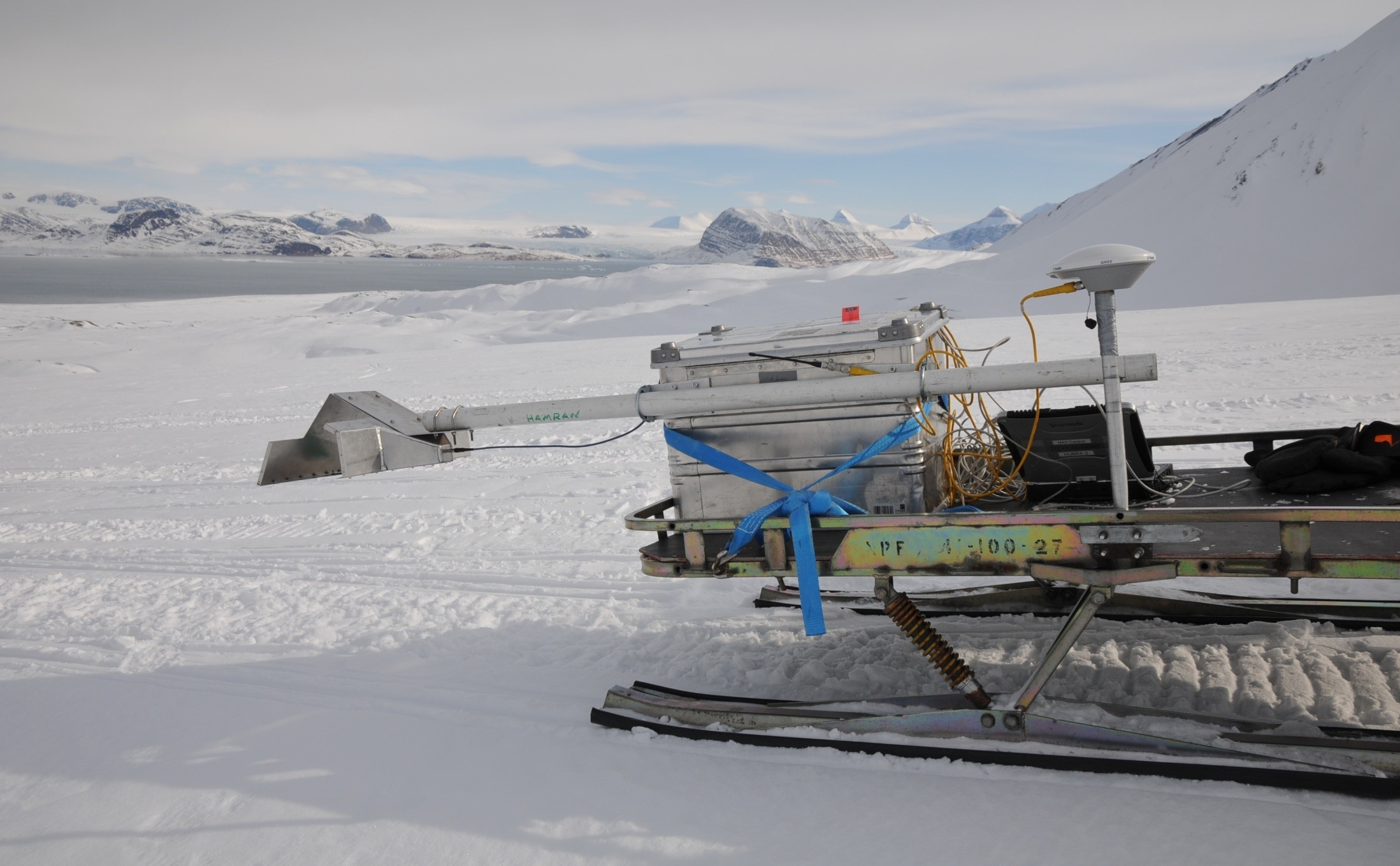 Photograph showing the prototype RIMFAX antenna attached to a snowmobile during tests in Svalbard, Norway.