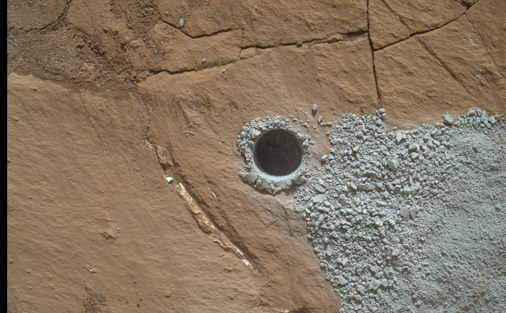 "NASA's Curiosity Mars Rover drilled this hole to collect sample material from a rock target called ""Buckskin"" on July 30, 2015, about a week prior to the third anniversary of the rover's landing on Mars. The diameter is slightly smaller than a U.S. dime."