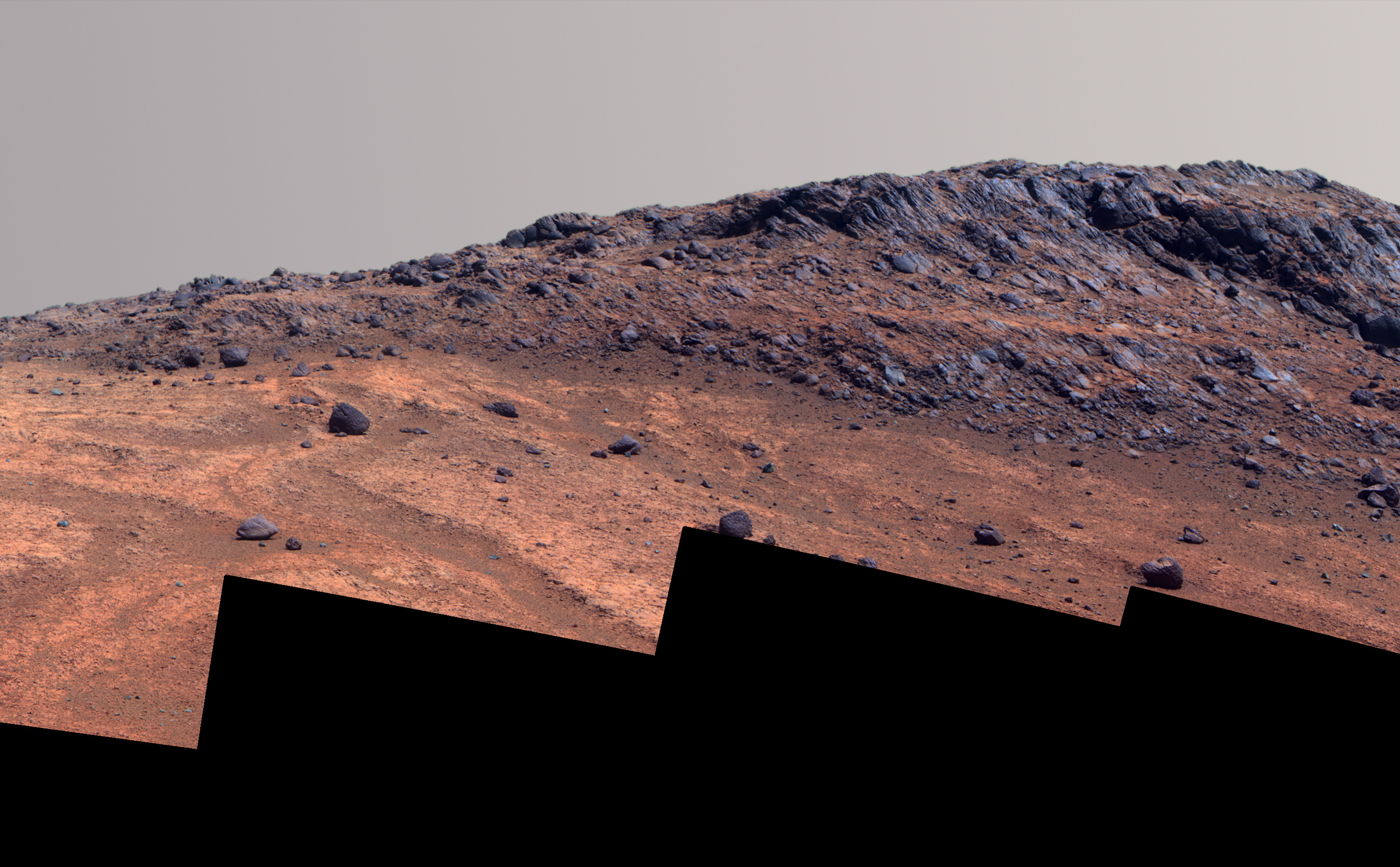 "This Martian scene shows contrasting textures and colors of ""Hinners Point,"" at the northern edge of ""Marathon Valley,"" and swirling reddish zones on the valley floor to the left."