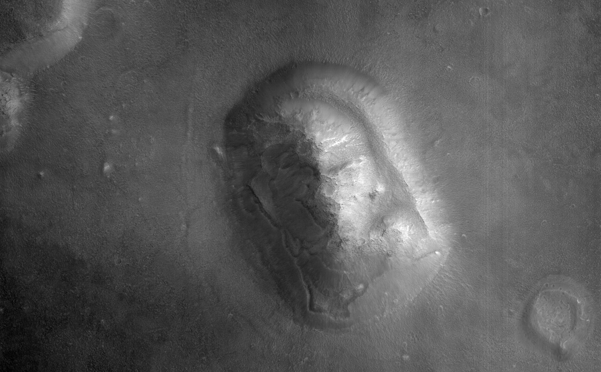 HiRISE captured this image of an eroded mesa made famous by its similarity to a human face in a Viking Orbiter image with much lower spatial resolution and a different lighting geometry.