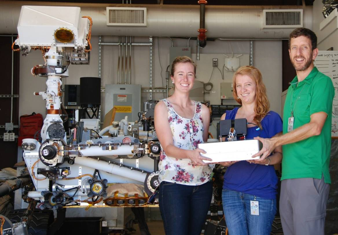 JPL researchers Jessica Creamer, Fernanda Mora and Peter Willis (left to right) pose with the Chemical Laptop, a device designed to detect amino acids and fatty acids. At left is a near-identical copy of the Curiosity rover, which has been on Mars since 2012.