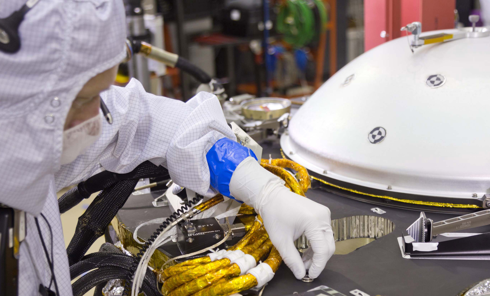 A spacecraft specialist in a clean room at Lockheed Martin Space Systems in Denver, where the InSight lander is being built, affixes a dime-size chip onto the lander deck in November 2015.