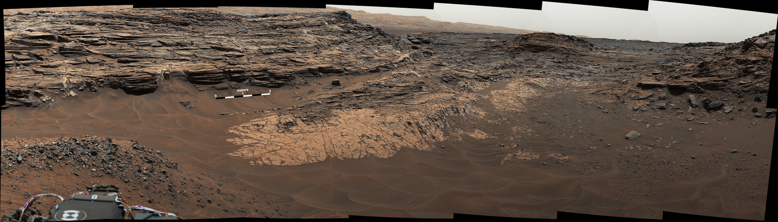 "This May 22, 2015, view from the Mast Camera (Mastcam) in NASA's Curiosity Mars rover shows the ""Marias Pass"" area where a lower and older geological unit of mudstone -- the pale zone in the center of the image -- lies in contact with an overlying geological unit of sandstone."