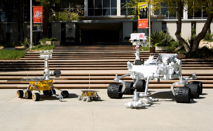 Full-scale models of three generations of NASA Mars rovers show the increase in size from the Sojourner rover of the Mars Pathfinder (center), to the twin Mars Exploration Rovers Spirit and Opportunity(left), to the Mars Science Laboratory rover (right).