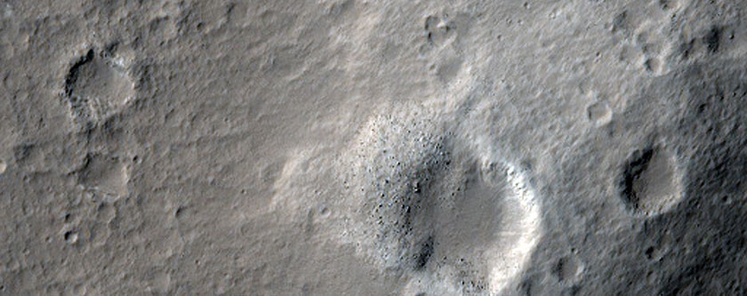 This area of Mars has a few gray craters, with white/light material surrounding it.