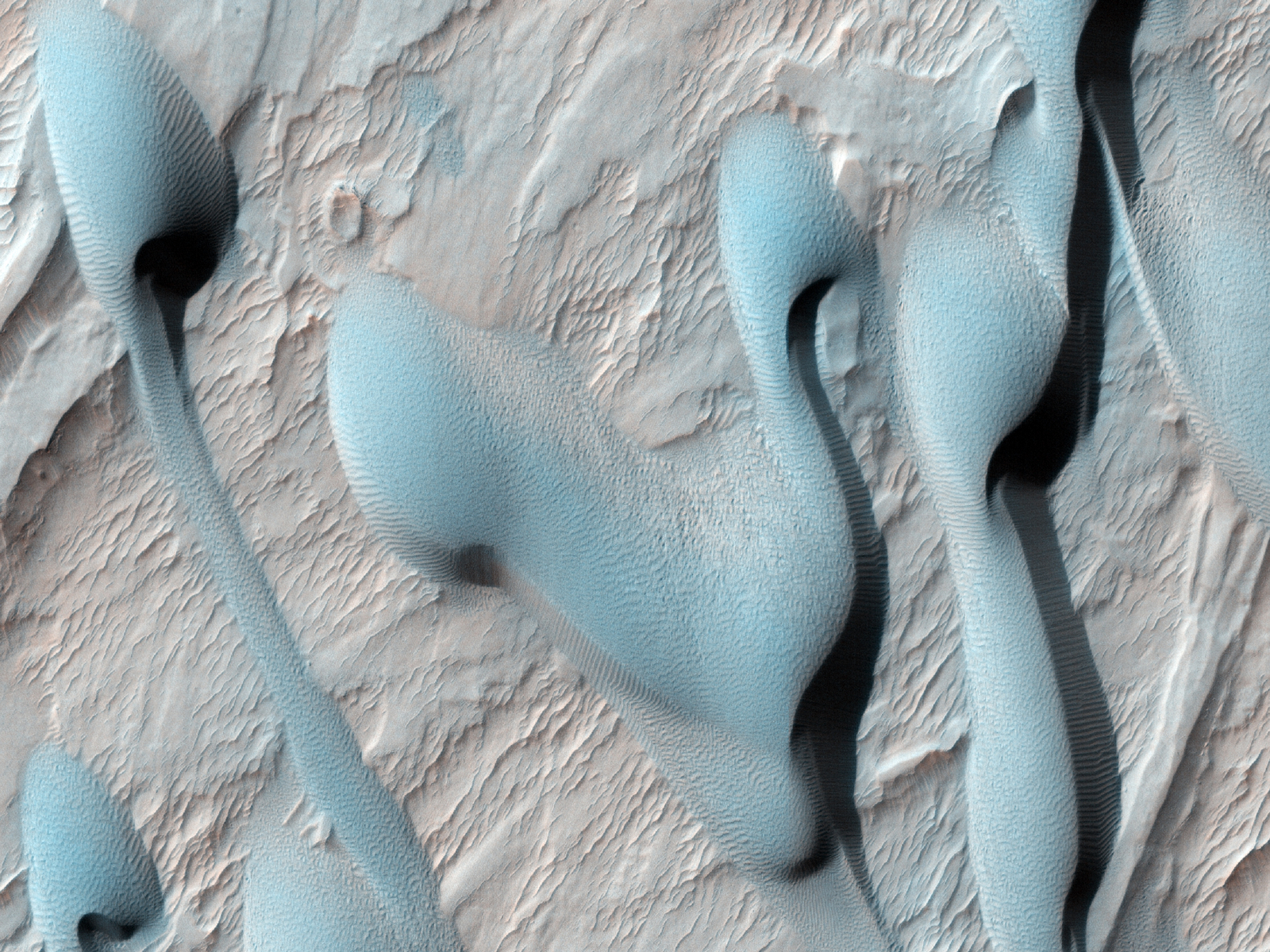 This scene shows dark sand dunes marching over the ridges created by an alluvial (water-deposited) fan in an impact crater.