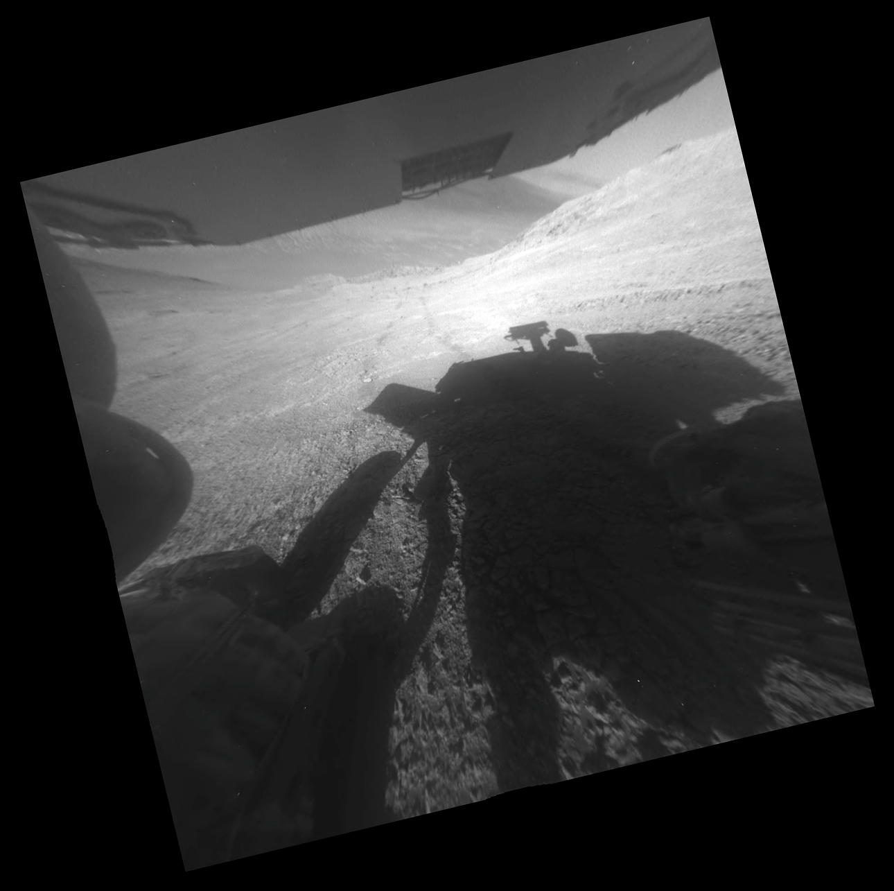 A shadow and tracks of NASA's Mars rover Opportunity appear in this March 22, 2016, image, which has been rotated 13.5 degrees to adjust for the tilt of the rover. The hillside descends to the left into 'Marathon Valley.' The floor of Endeavour Crater is seen beneath the underside of a solar panel.