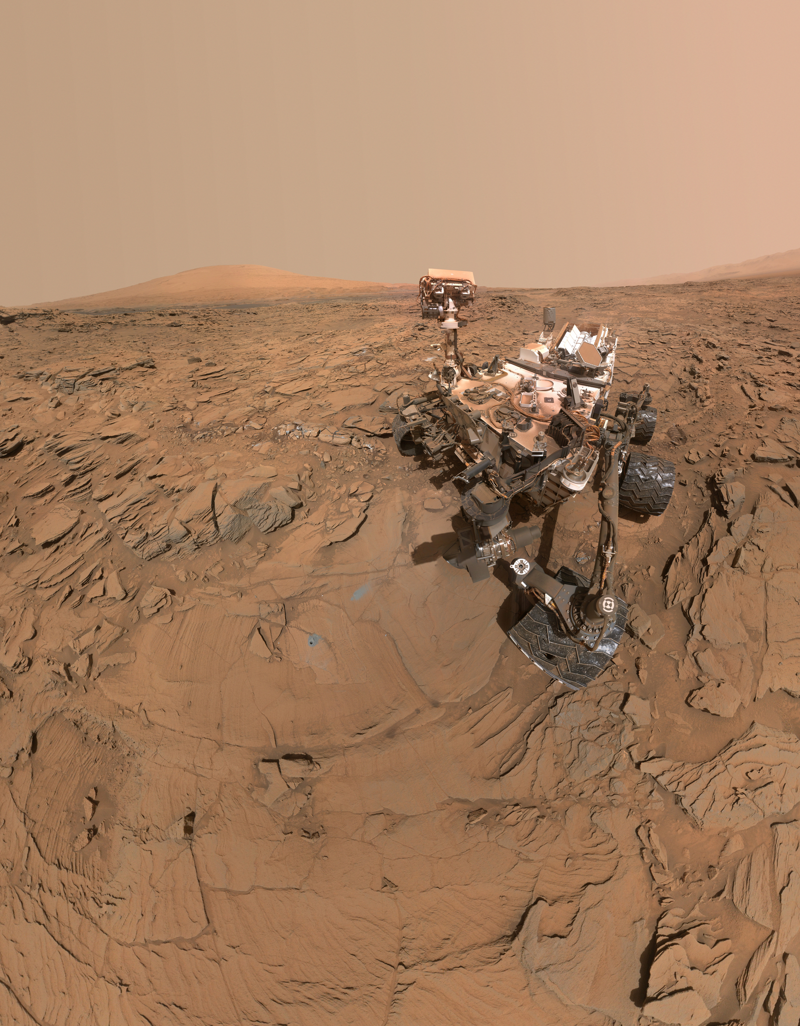 "The top of the rover's mast faces away in this May 11, 2016, self-portrait of NASA's Curiosity Mars rover, which shows the vehicle at the ""Okoruso"" drilling site on lower Mount Sharp. The scene is a mosaic of multiple images taken with the arm-mounted Mars Hands Lens Imager (MAHLI)."