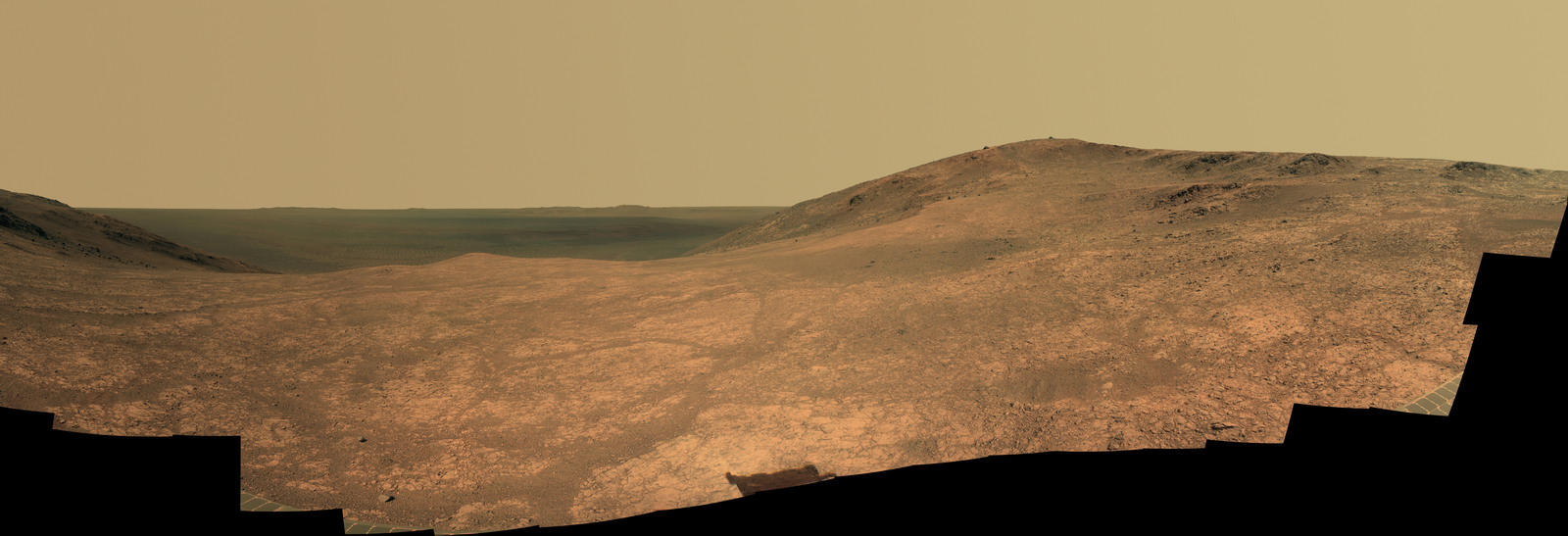 """Marathon Valley"" on Mars opens to a view across Endeavour Crater in this scene from the Pancam of NASA's Mars rover Opportunity. The scene merges many exposures taken during April and May 2016. The view spans from north (left) to west-southwest. Its foreground shows the valley's fractured texture."