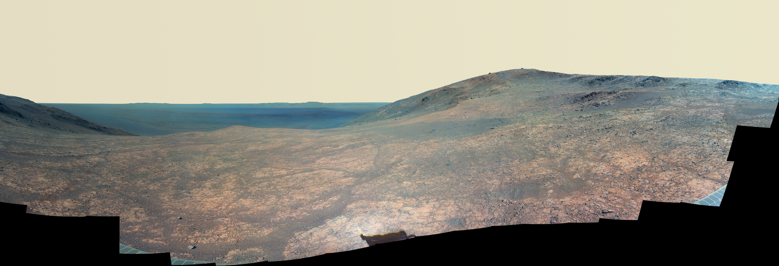 """Marathon Valley"" on Mars opens to a view across Endeavour Crater in this enhanced-color version of a scene from the Pancam of NASA's Mars Exploration Rover Opportunity. The scene merges many exposures taken during April and May 2016. The foreground shows the fractured texture of the valley."