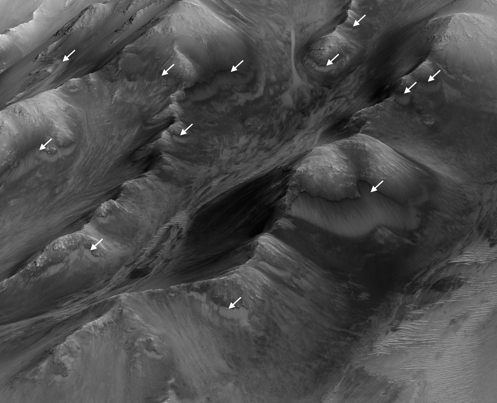 "The white arrows indicate locations in this scene where numerous seasonal dark streaks, called ""recurring slope lineae,"" have been identified in the Coprates Montes area of Mars' Valles Marineris by repeated observations from orbit."