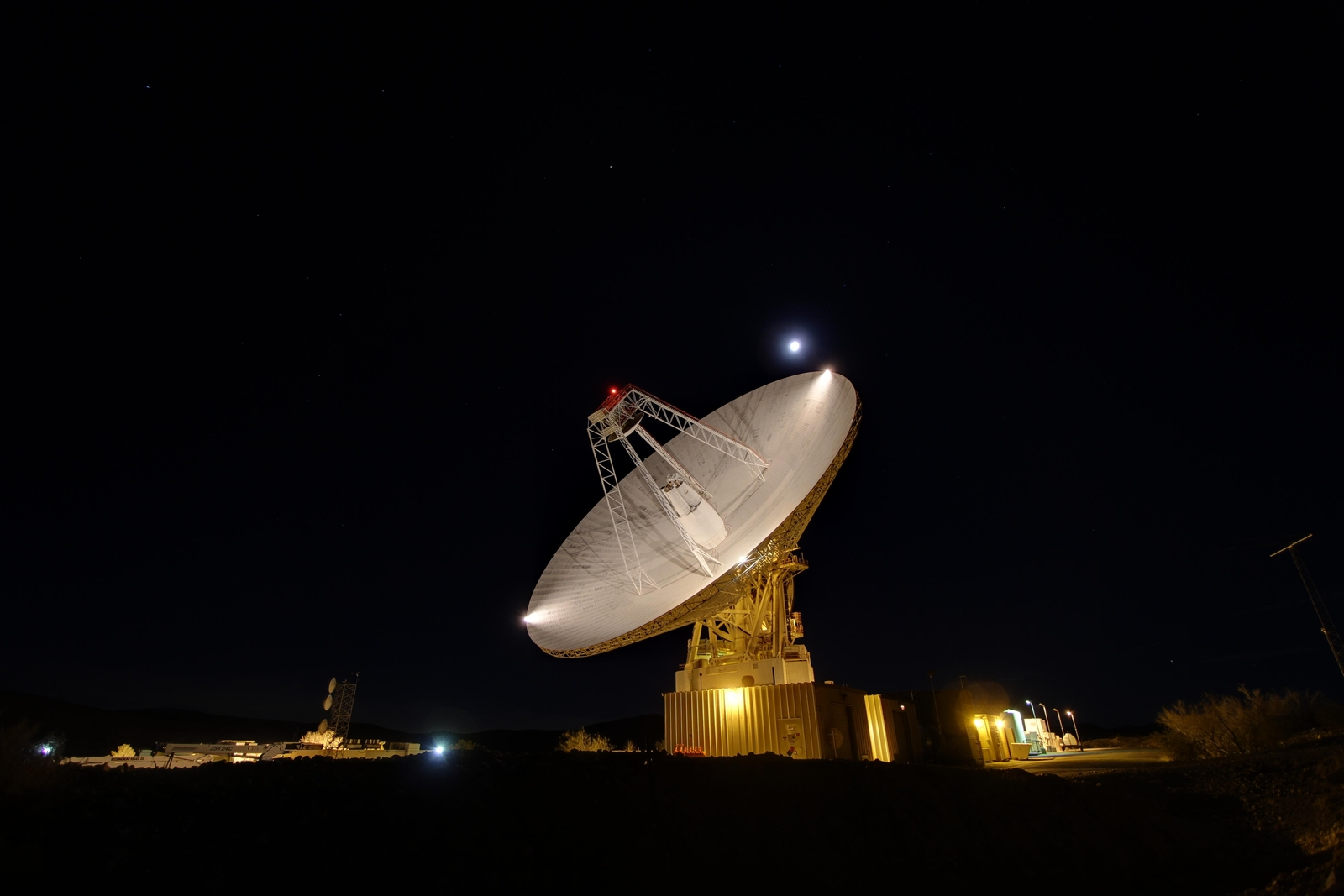 Goldstone's 230-foot (70-m) antenna tracks under a full moon. This photograph was taken on Jan. 11, 2012.