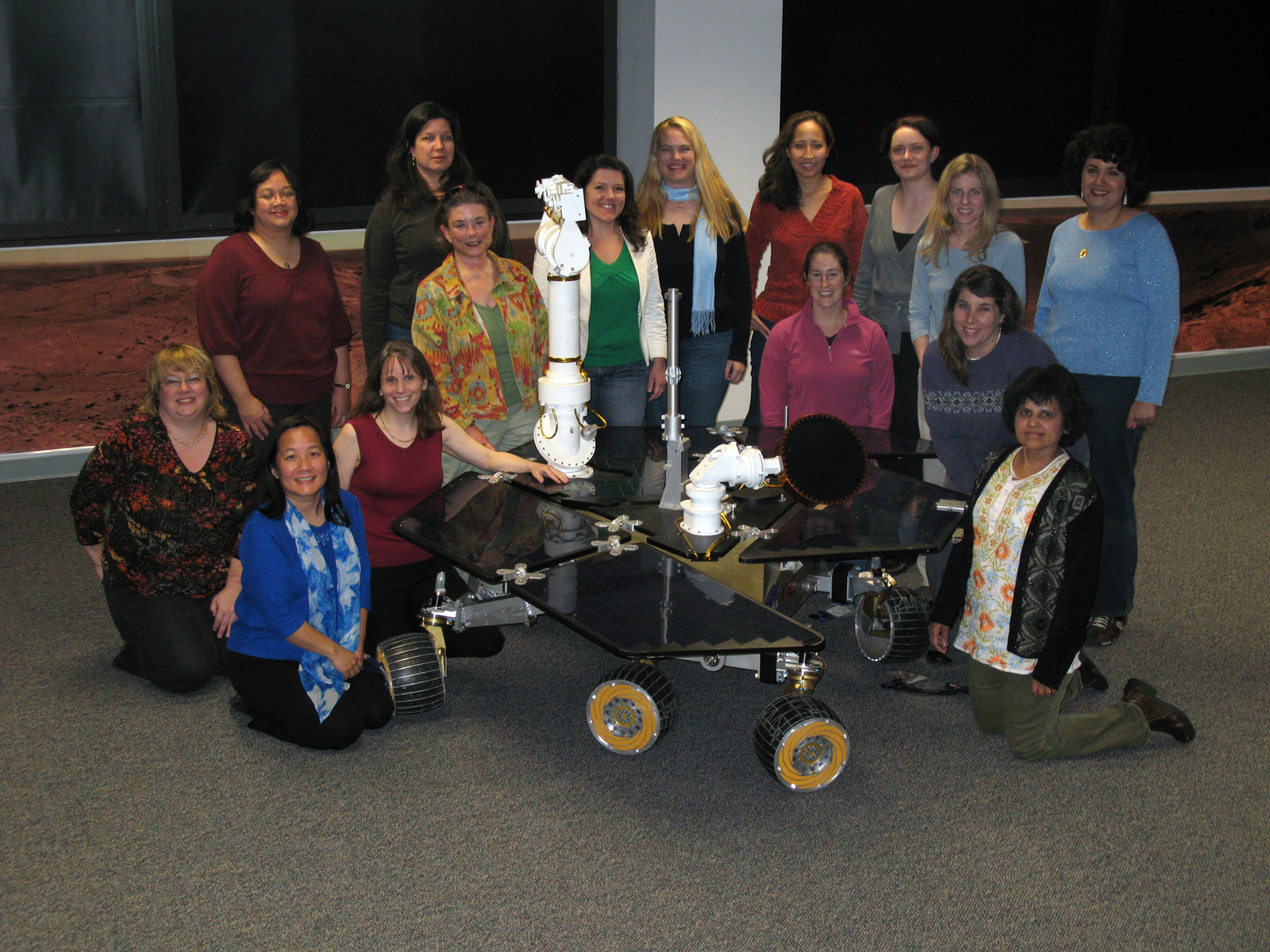 This photo shows fifteen of the women engineers and scientists who work on the Mars Exploration Rover. They are standing behind or kneeling beside a precise replica of the rover in the mission control room.
