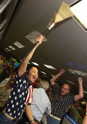 Dr. Wayne Lee, chief engineer for development of the Mars Exploration Rover's descent and landing systems proudly waves a broom, indicating a clean martian sweep.